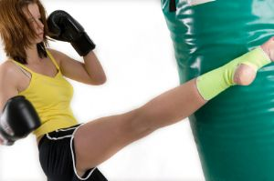 Woman practicing kick-boxing in the gym.